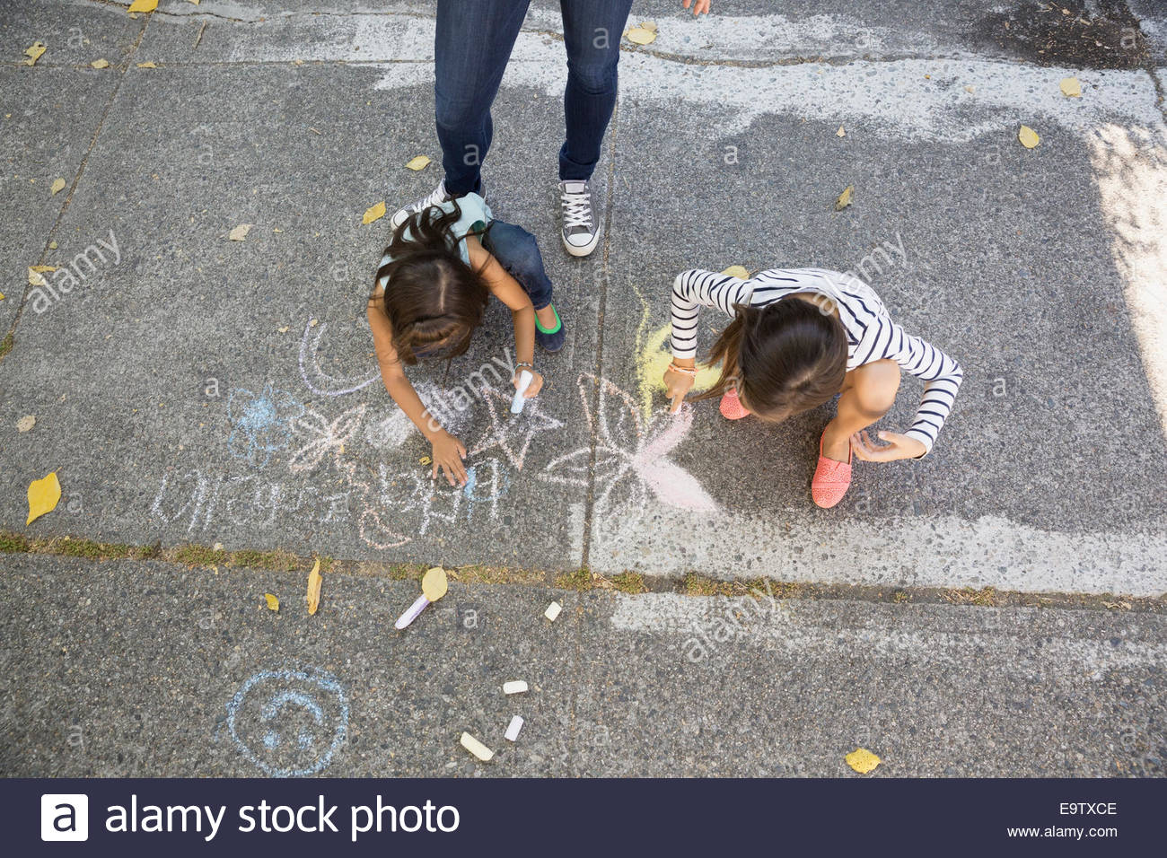 Sisters drawing with sidewalk chalk Stock Photo