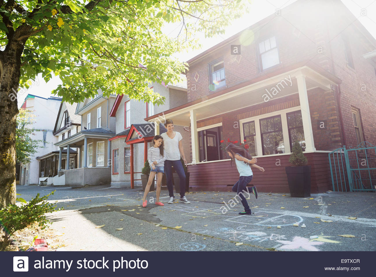 Mother and daughters playing hopscotch on sunny sidewalk - Stock Image