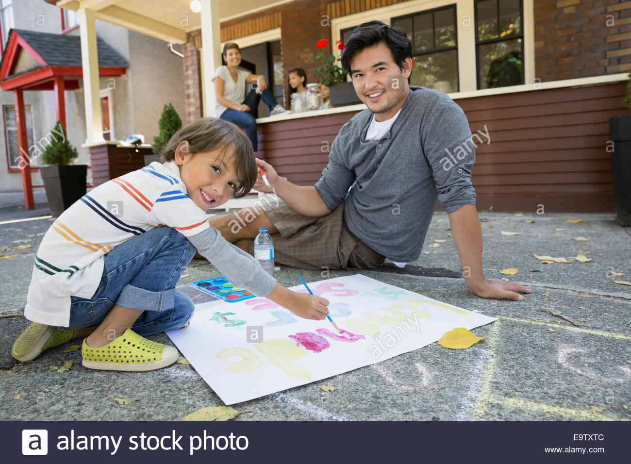 Father and son painting lemonade stand sign - Stock Image