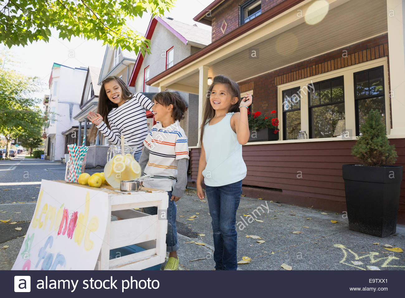 Brother and sisters at lemonade stand outside house - Stock Image