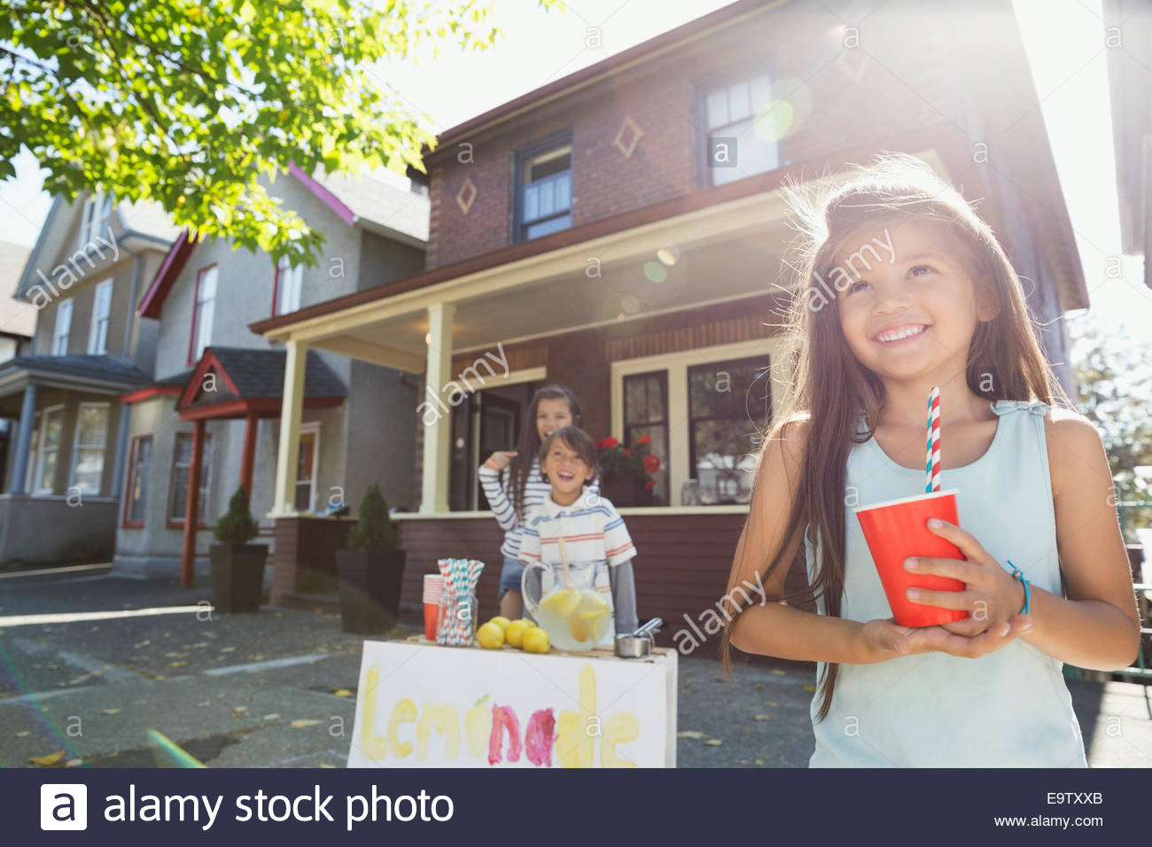Smiling girl with cup at lemonade stand - Stock Image