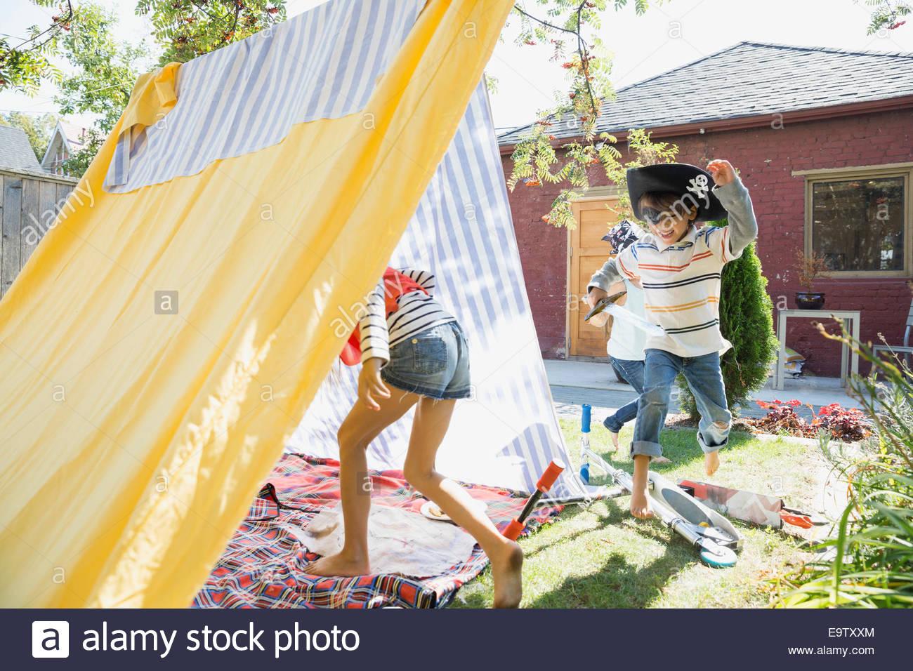 Children playing pirates in backyard fort - Stock Image