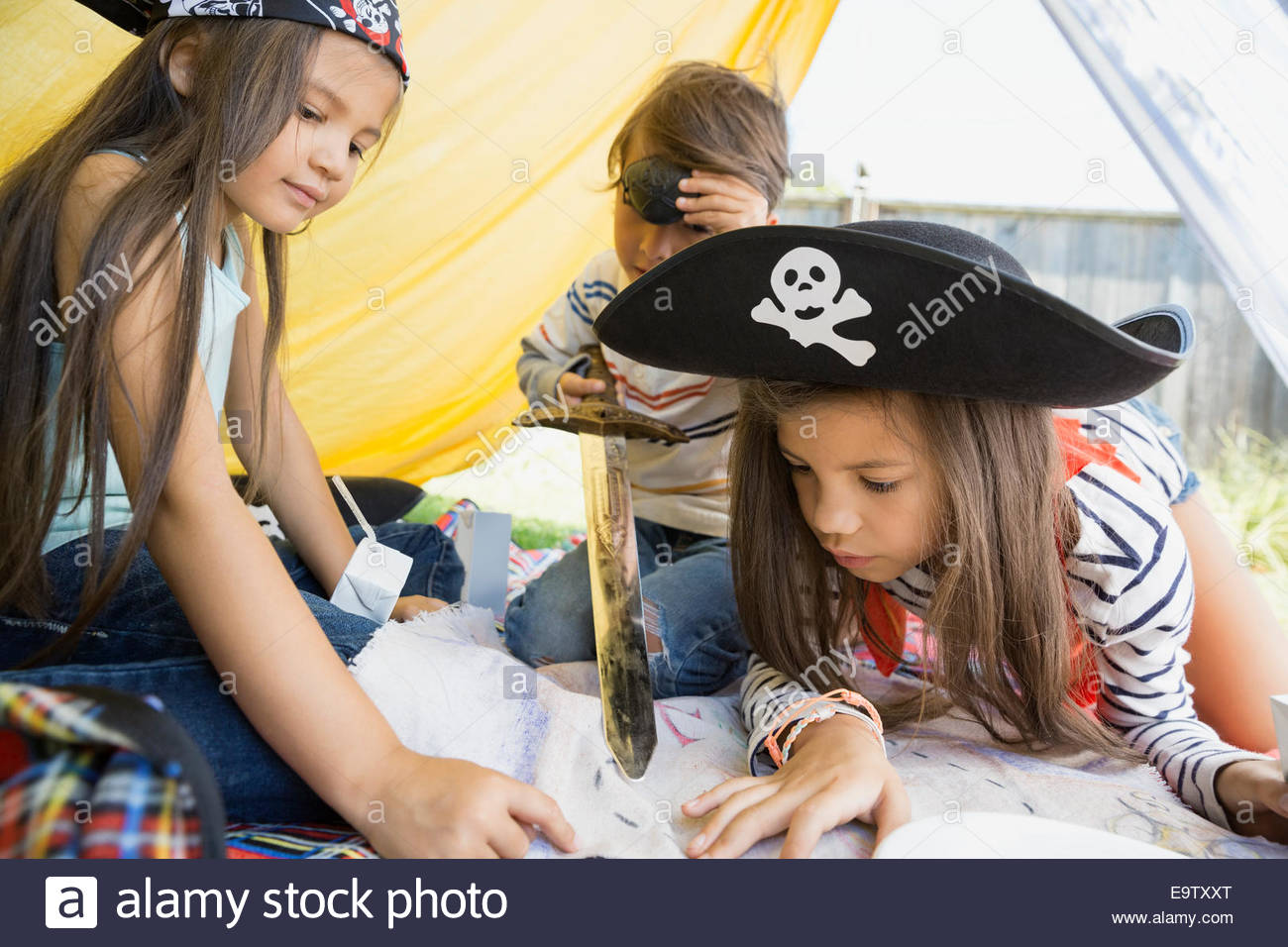 Children playing pirates and viewing treasure map - Stock Image