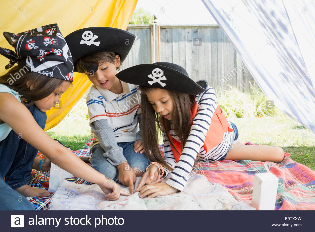 Children playing pirates and pointing at treasure map - Stock Image