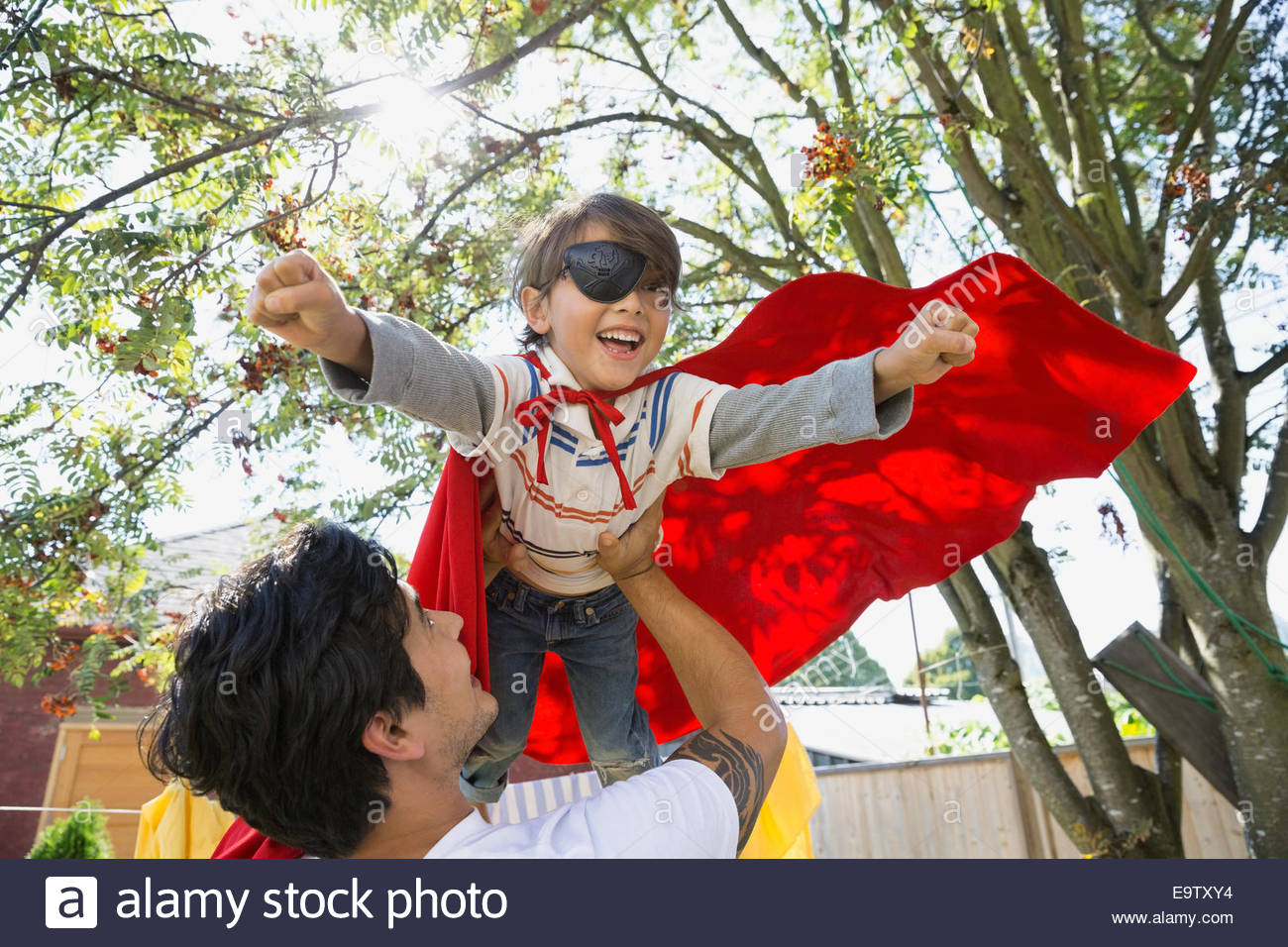 Father flying son in superhero cape overhead - Stock Image