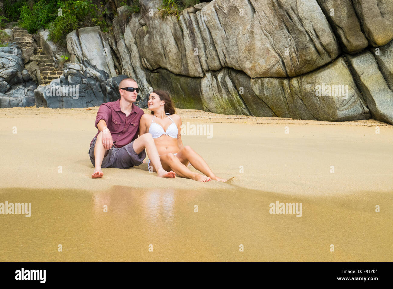 Young couple sitting in the sand at remote beach at Mexico's pacific coast in Bahia de Banderas. - Stock Image