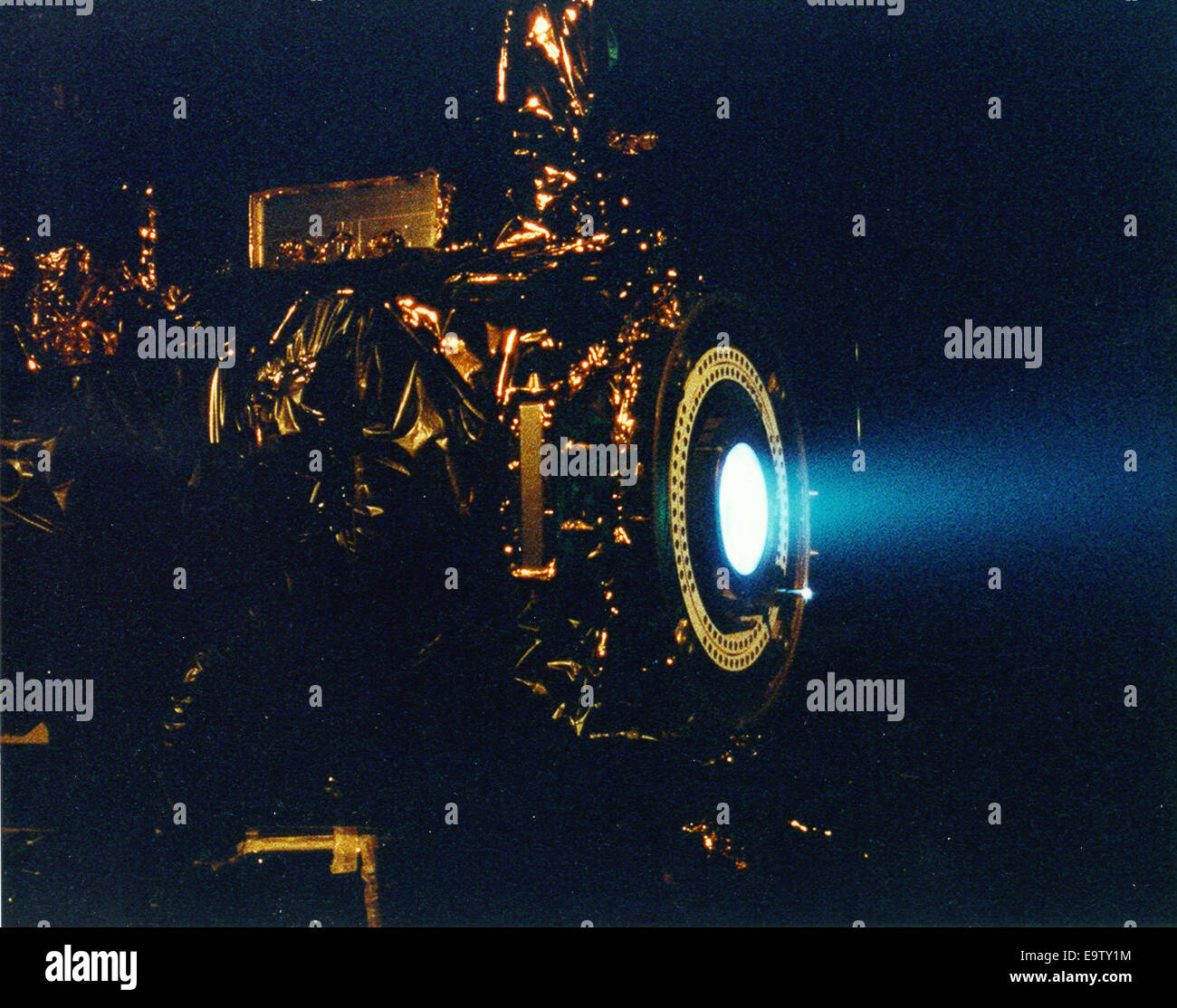 This image of a xenon ion engine, photographed through a port of the vacuum chamber where it was being tested at - Stock Image
