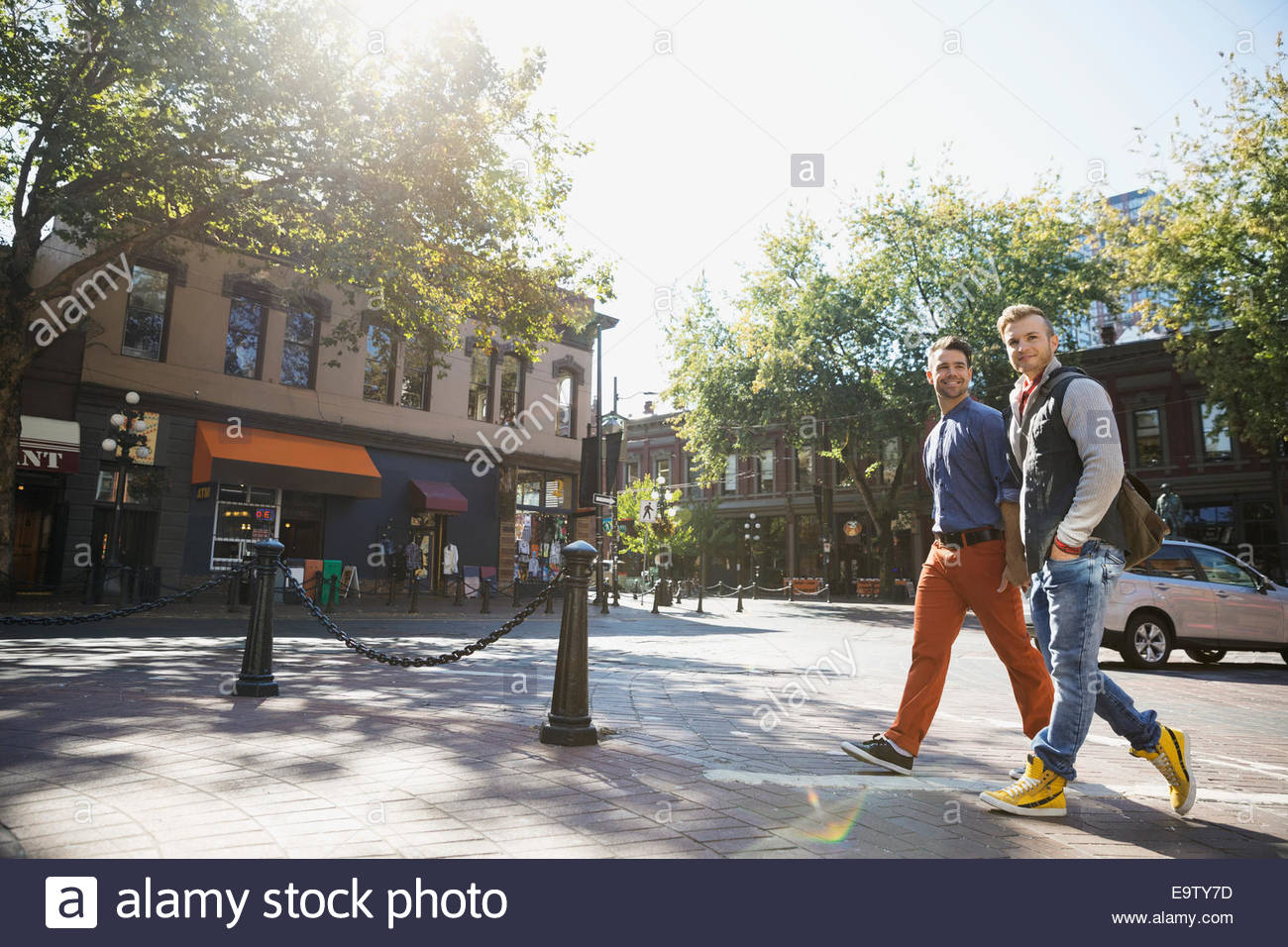 Homosexual couple walking on sunny urban street - Stock Image