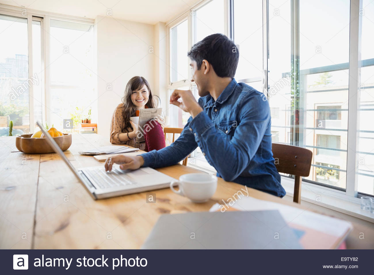Couple reading and using laptop at table - Stock Image