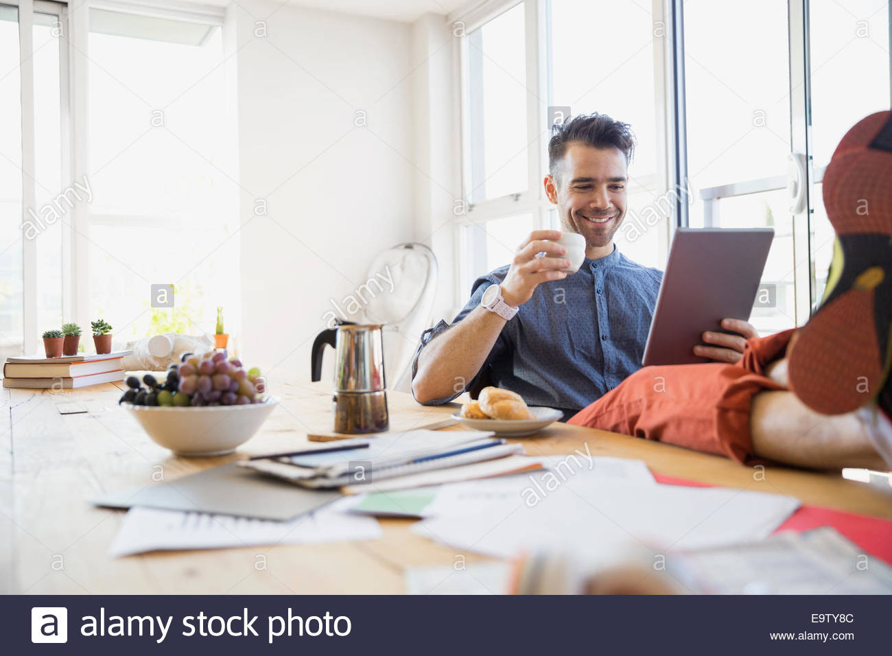 Man using digital tablet with feet on table - Stock Image