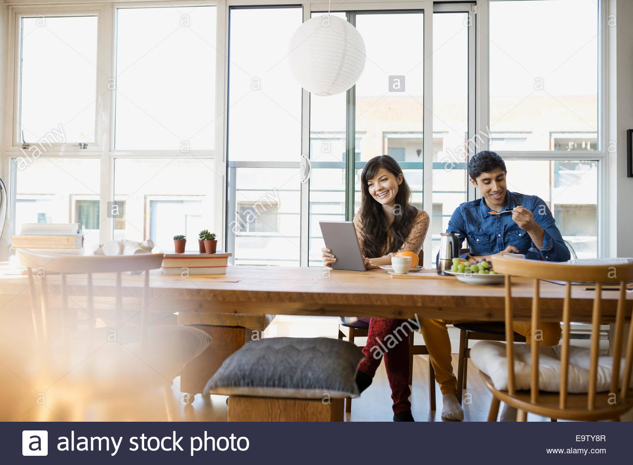 Couple using digital tablet and eating at table - Stock Image