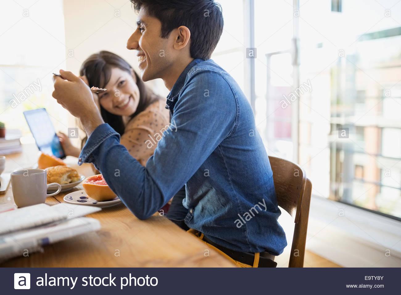 Couple enjoying breakfast at table - Stock Image