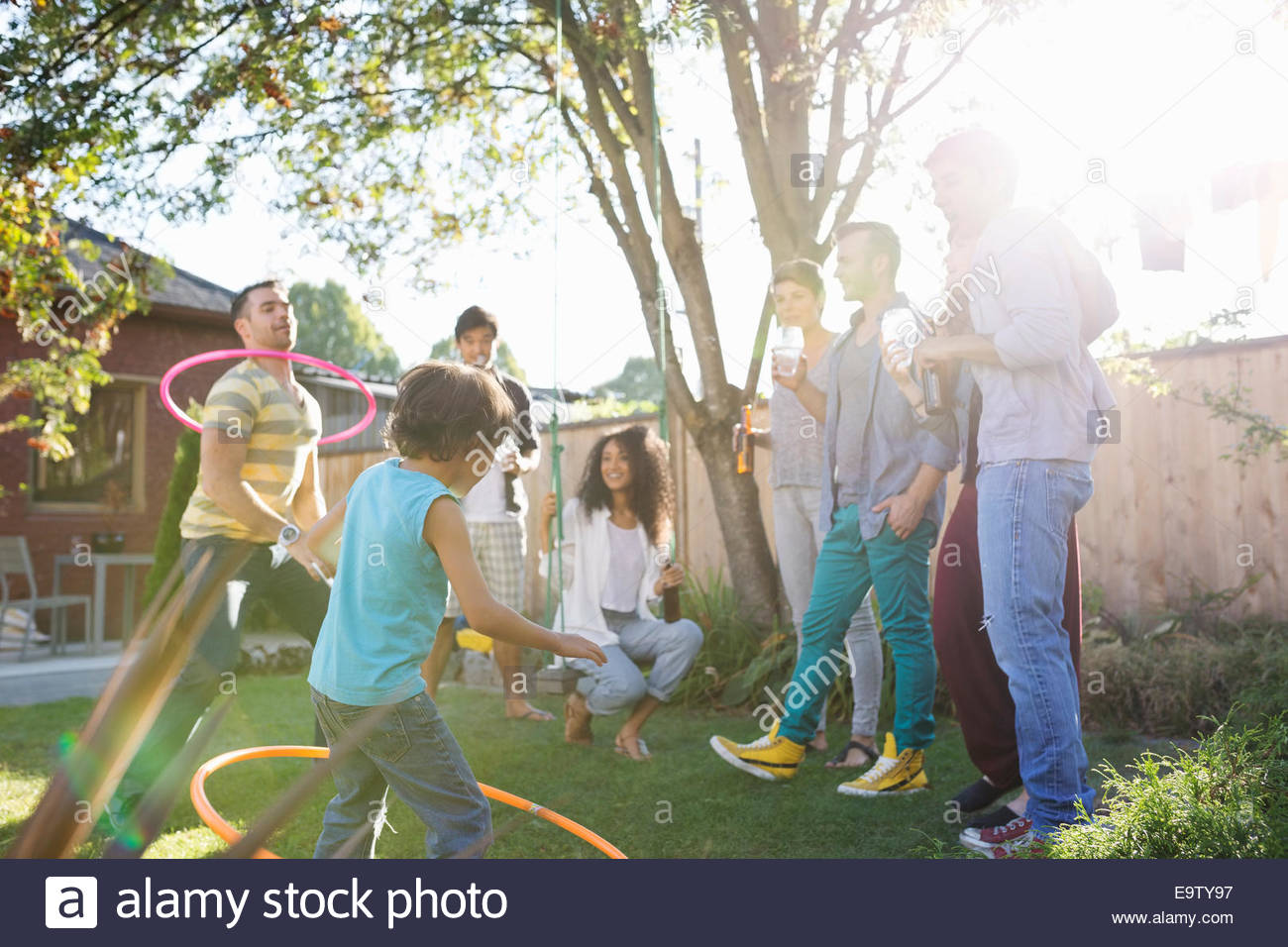Friends playing with plastic hoops in sunny backyard - Stock Image