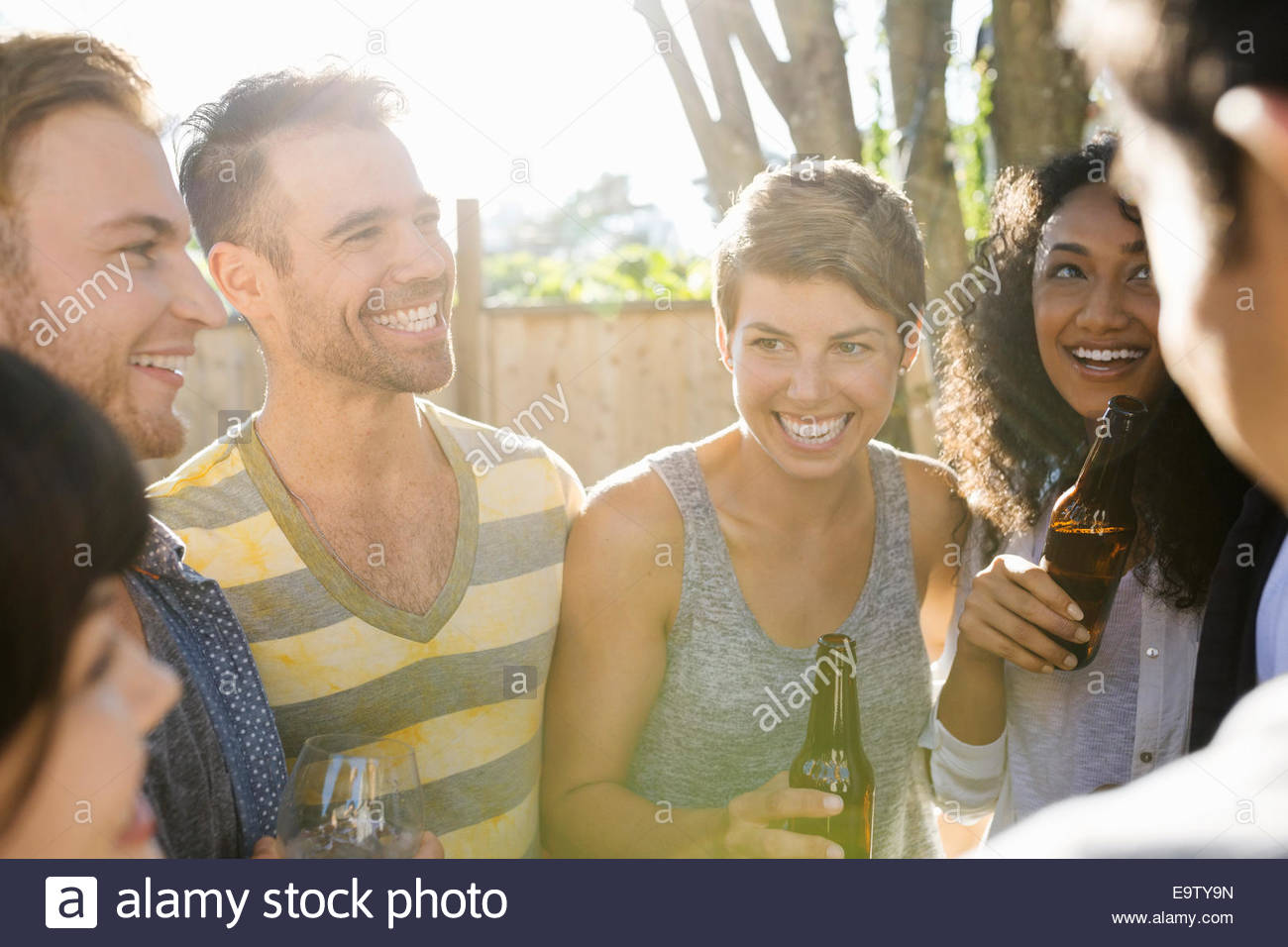 Friends drinking and hanging out at backyard barbecue - Stock Image