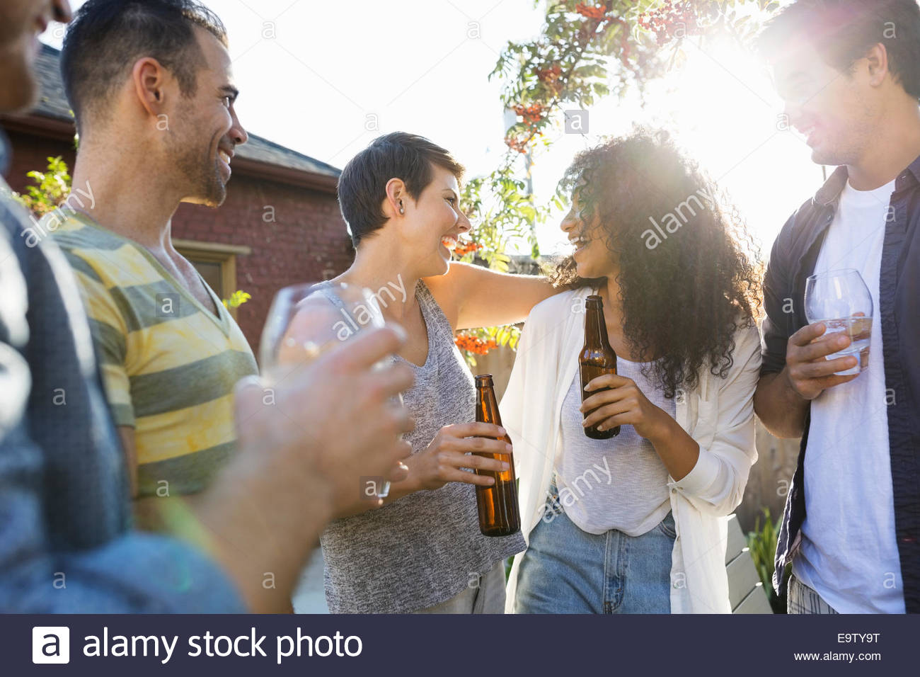 Friends drinking and hanging out at backyard barbecue Stock Photo