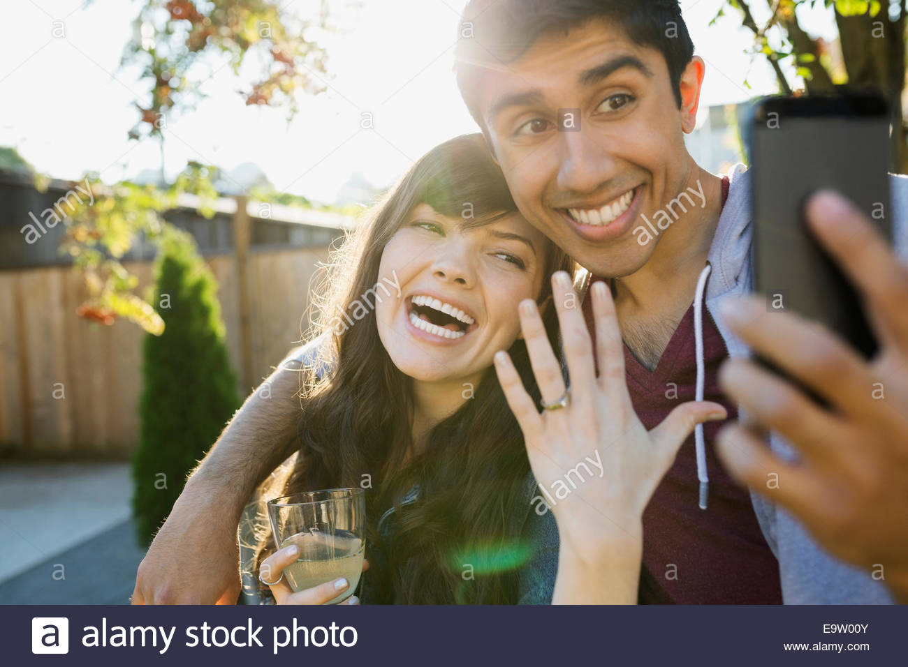 Enthusiastic couple taking selfie of engagement ring - Stock Image