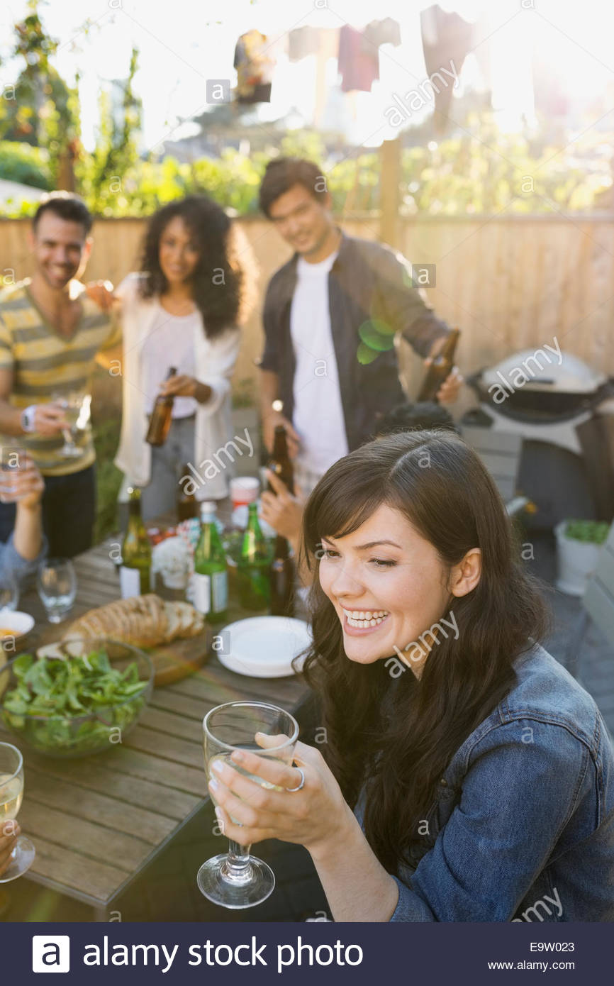 Smiling woman drinking wine at backyard barbecue - Stock Image