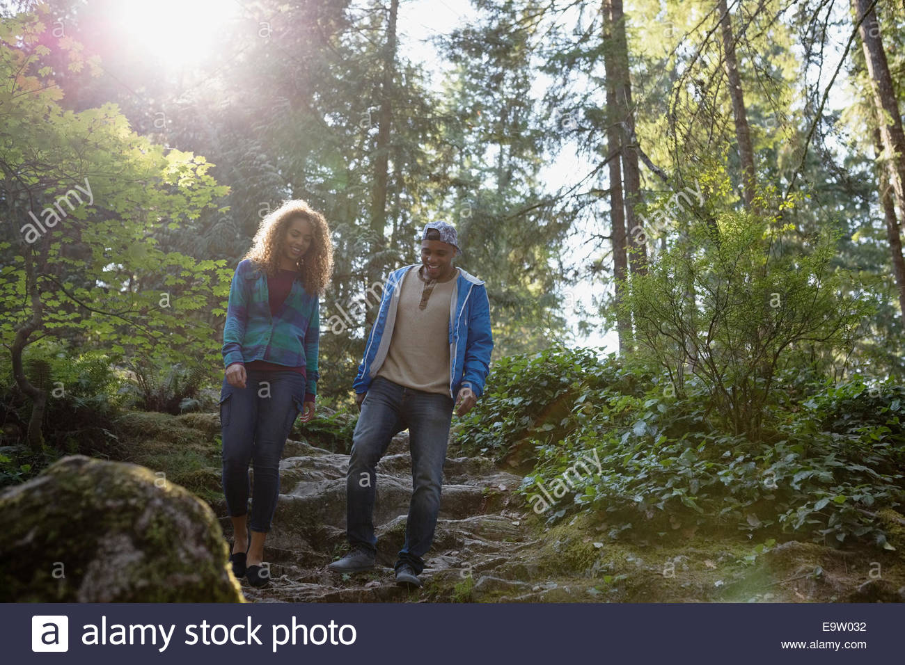Young couple hiking down path in woods - Stock Image