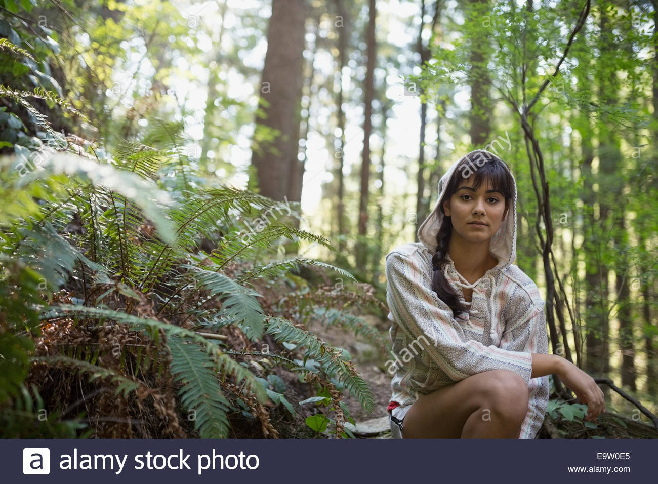 Portrait of young woman wearing hoody in woods - Stock Image