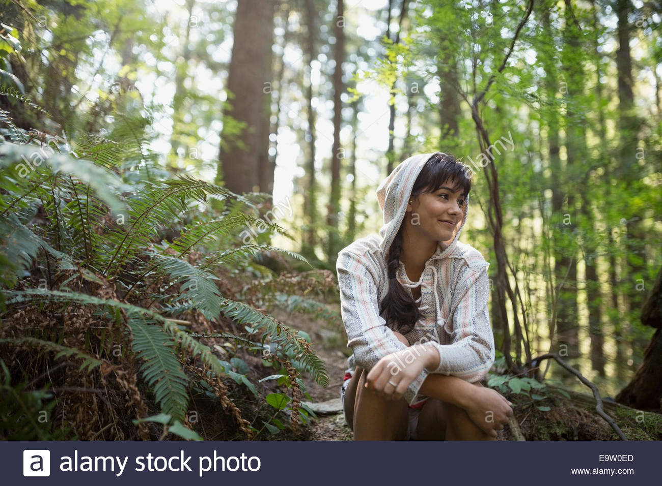 Young woman wearing hoody in woods - Stock Image