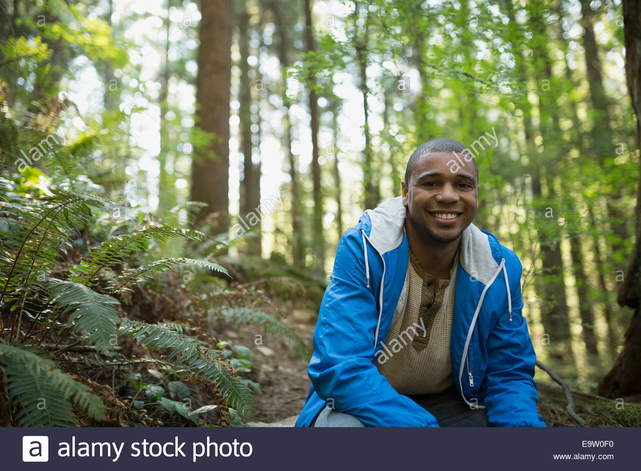 Portrait of young man smiling in woods - Stock Image
