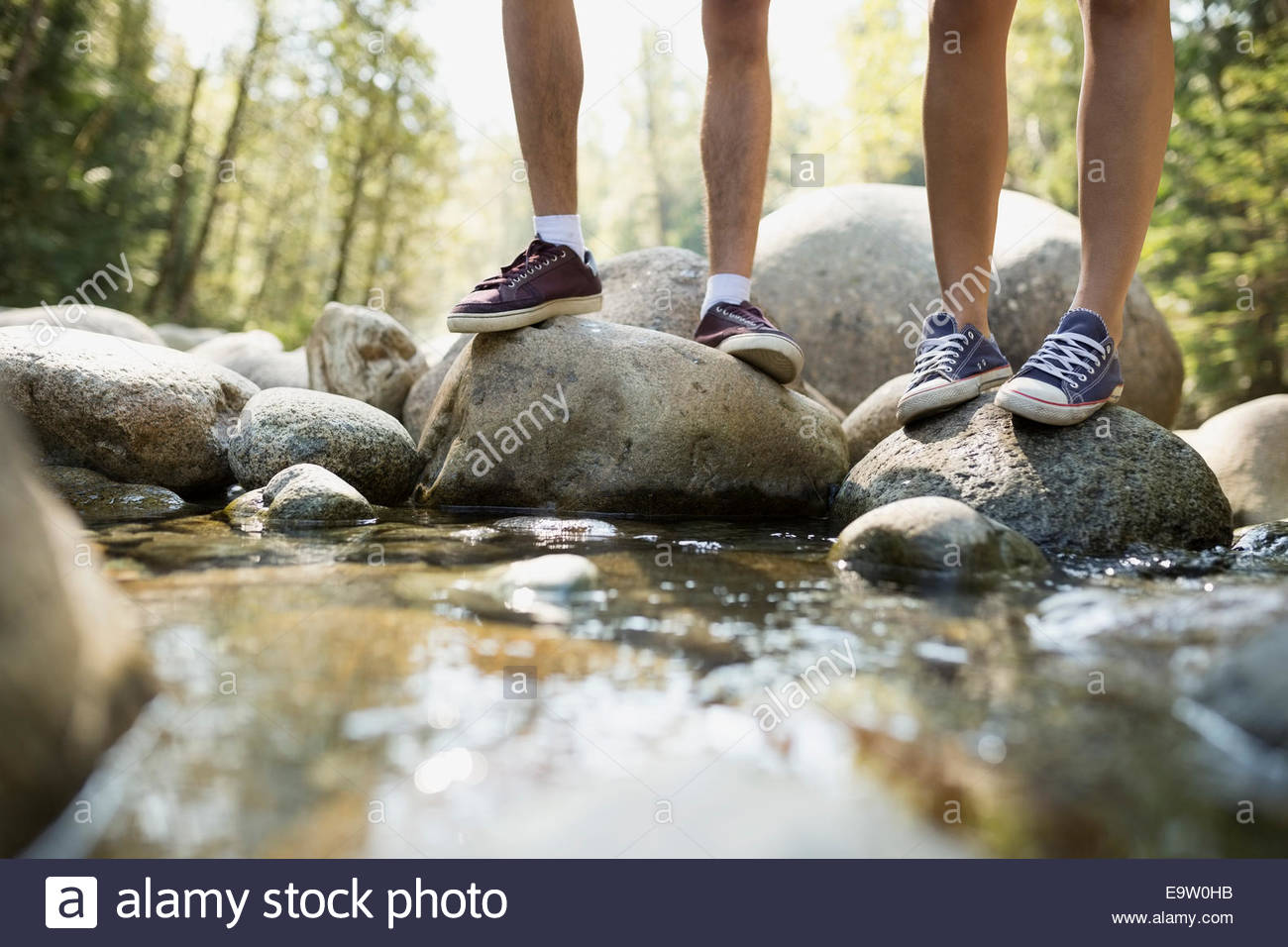 Friends standing on rocks in creek - Stock Image