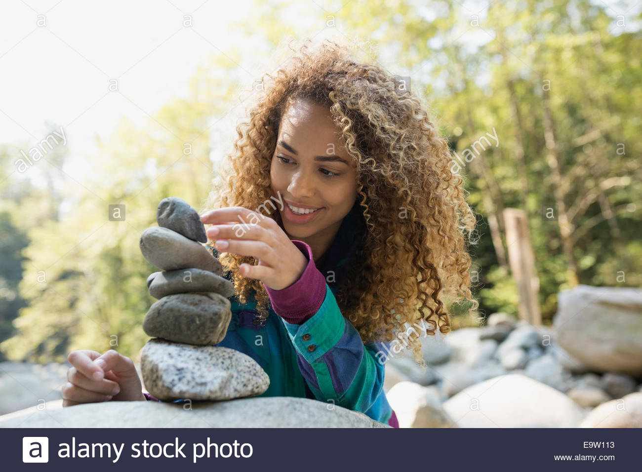 Young woman stacking stones in woods - Stock Image