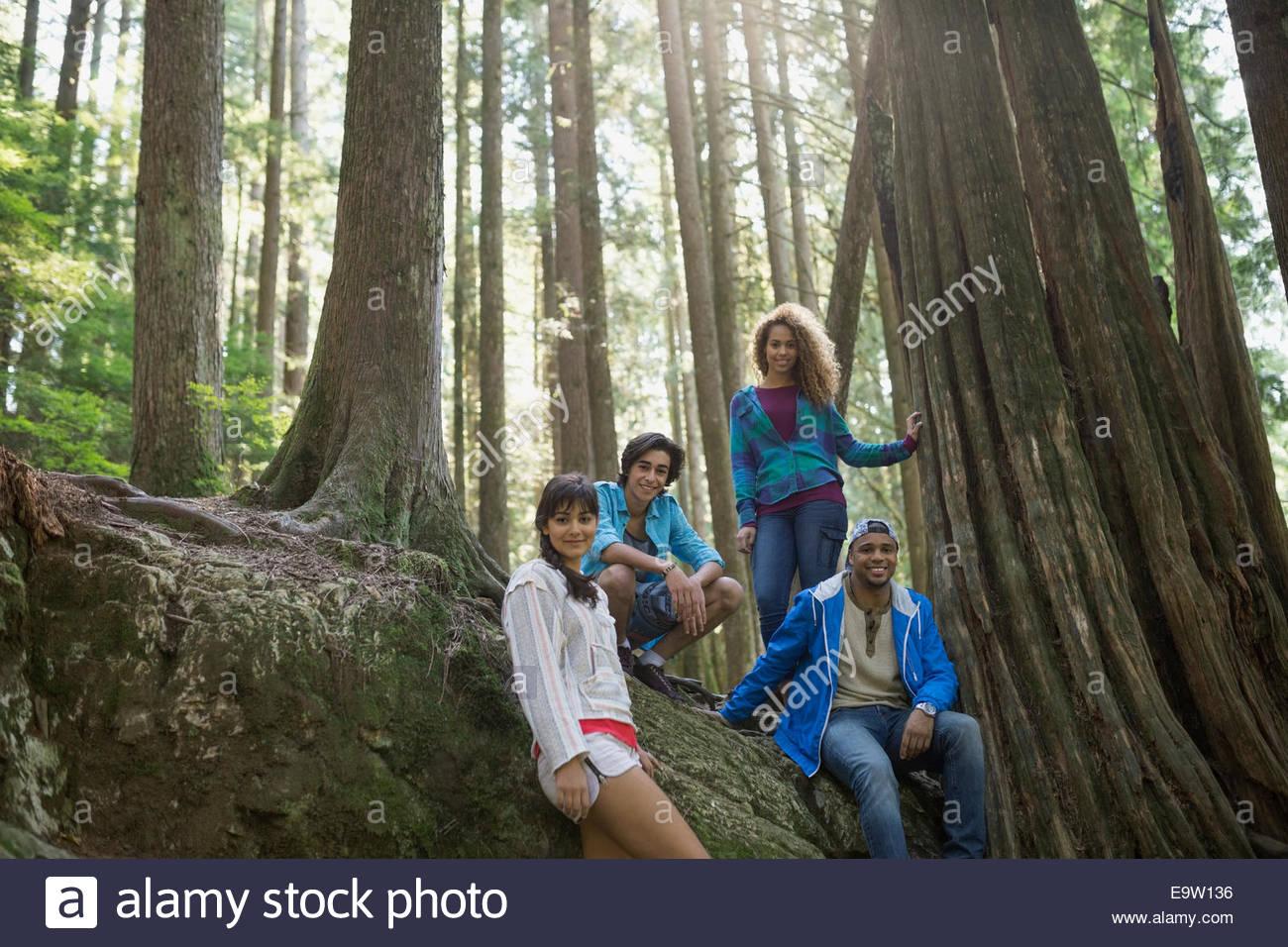 Portrait of friends below trees in woods - Stock Image