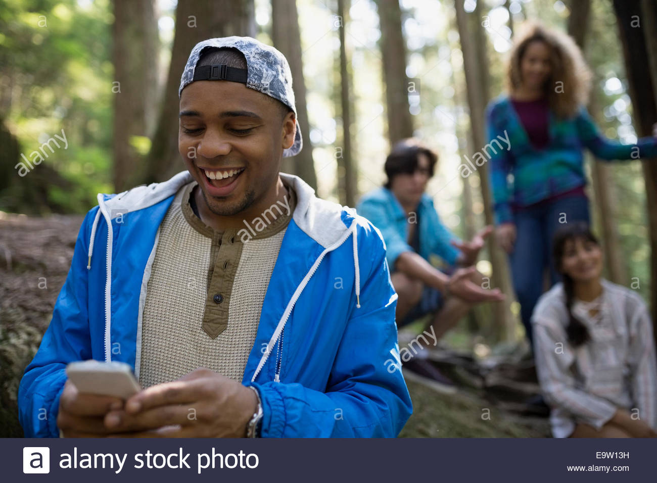 Enthusiastic young man using cell phone in woods - Stock Image