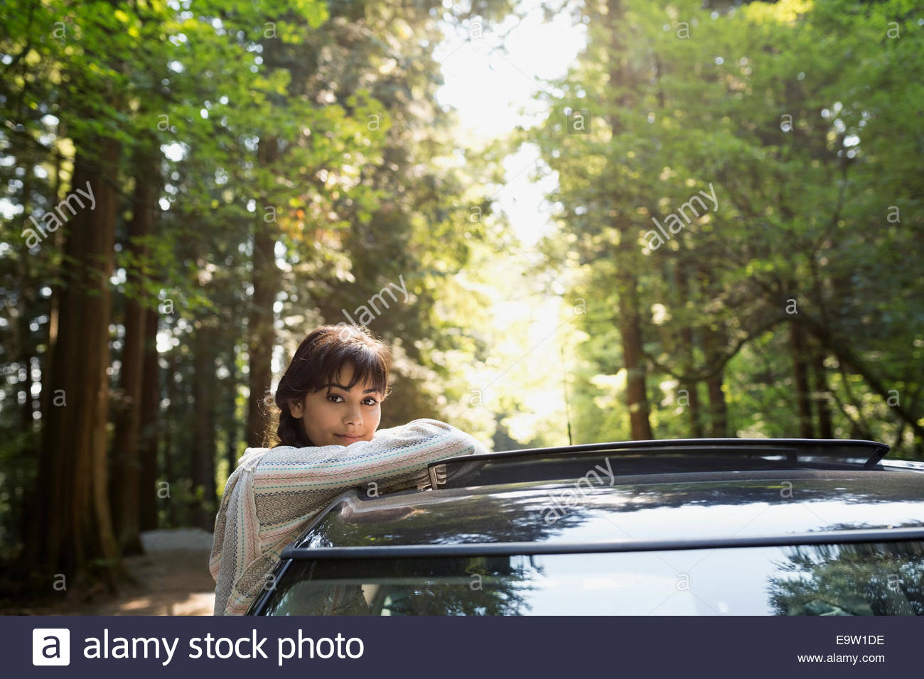 Portrait of woman leaning on car in woods - Stock Image