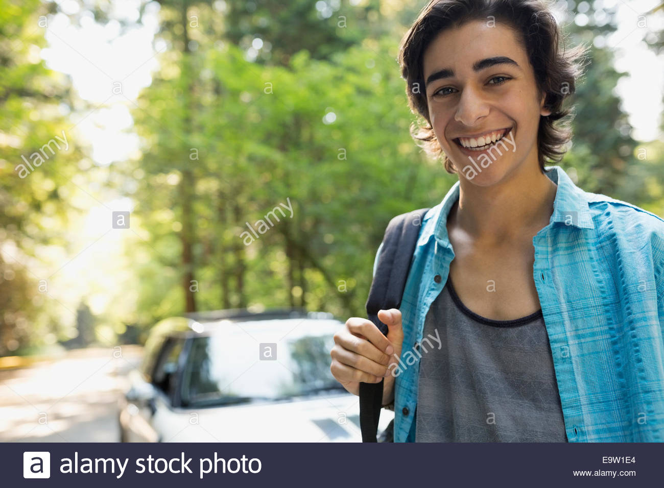Portrait of smiling teenage boy in woods - Stock Image