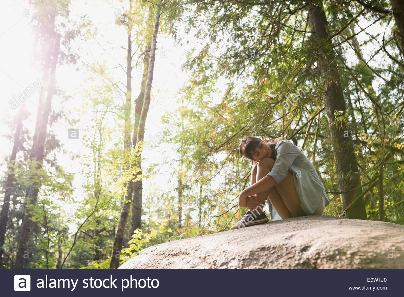 Serene woman resting on rock in sunny woods - Stock Image