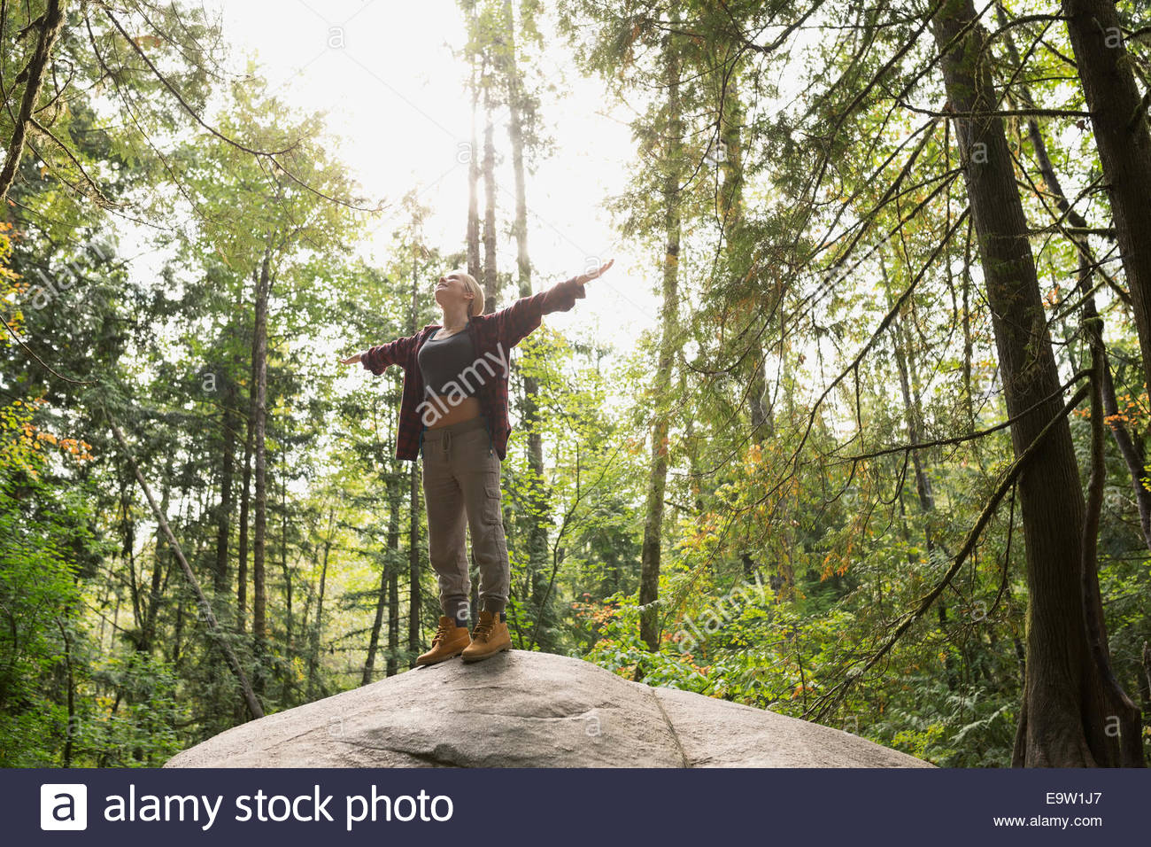 Woman with arms outstretched on rock in woods - Stock Image