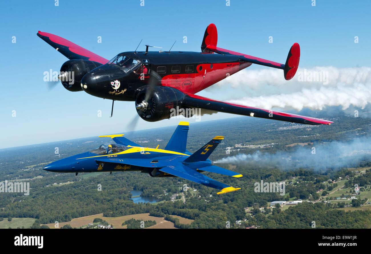A U.S. Navy F/A-18 Hornet aircraft assigned to the Blue Angels  flies alongside Younkin Air Show's performer Matt Stock Photo