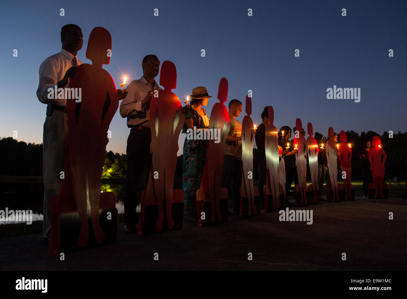 Volunteers hold cardboard references to domestic violence victims during a candlelight vigil Oct. 21, 2014, at the Stock Photo