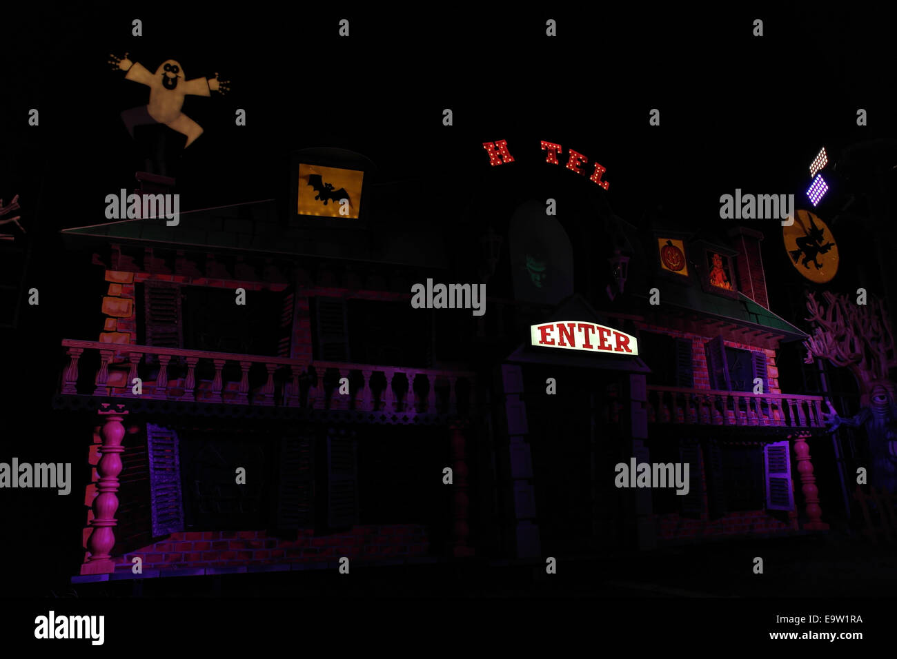 Night view purple lights Haunted Hotel Tableau with Frankenstein's Monster holograph looking down, Blackpool - Stock Image