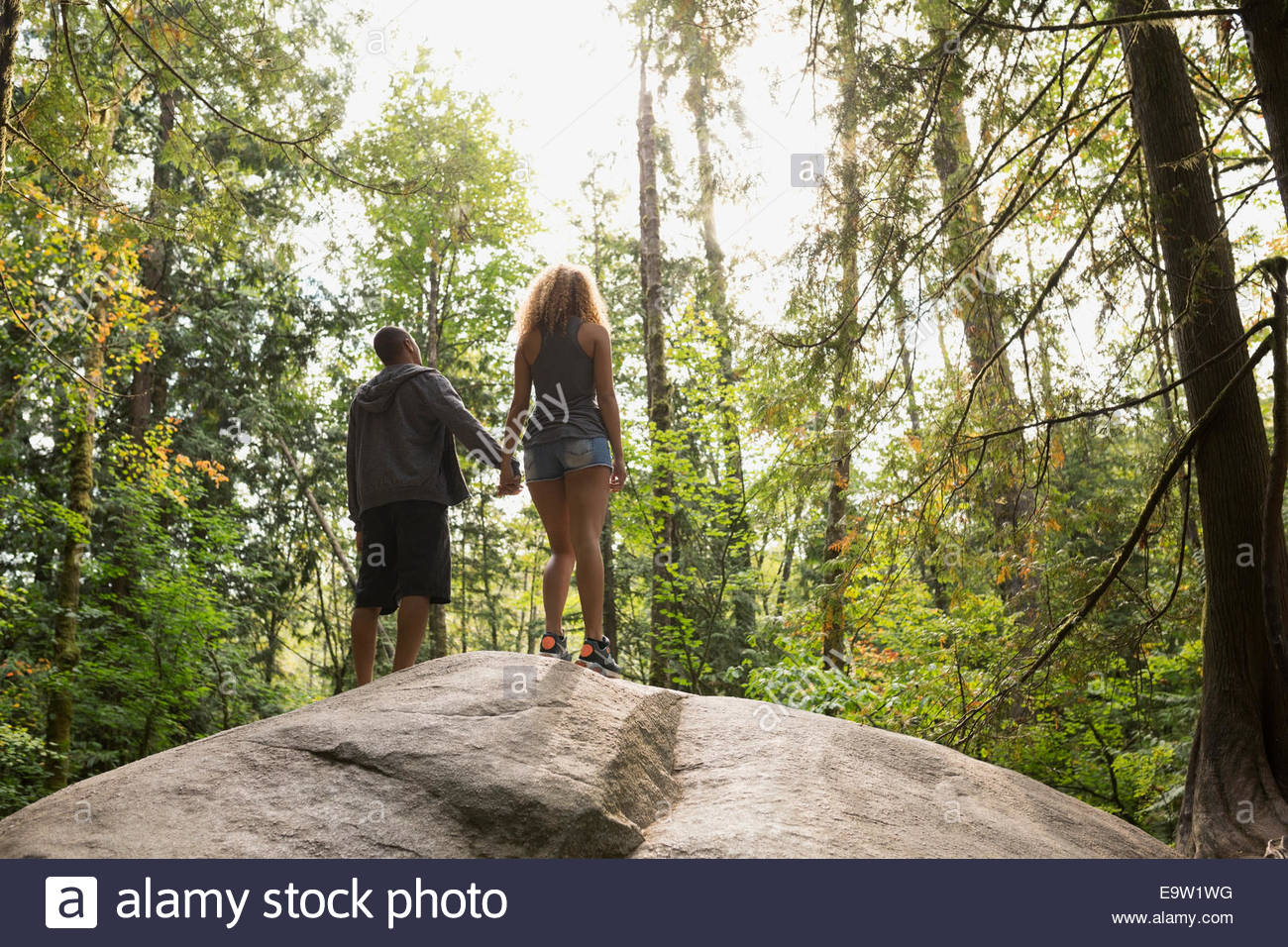 Couple holding hands on rock in sunny woods - Stock Image