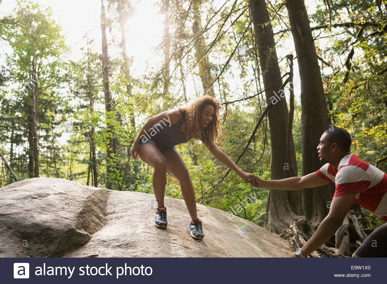 Couple holding hands on large rock in woods - Stock Image