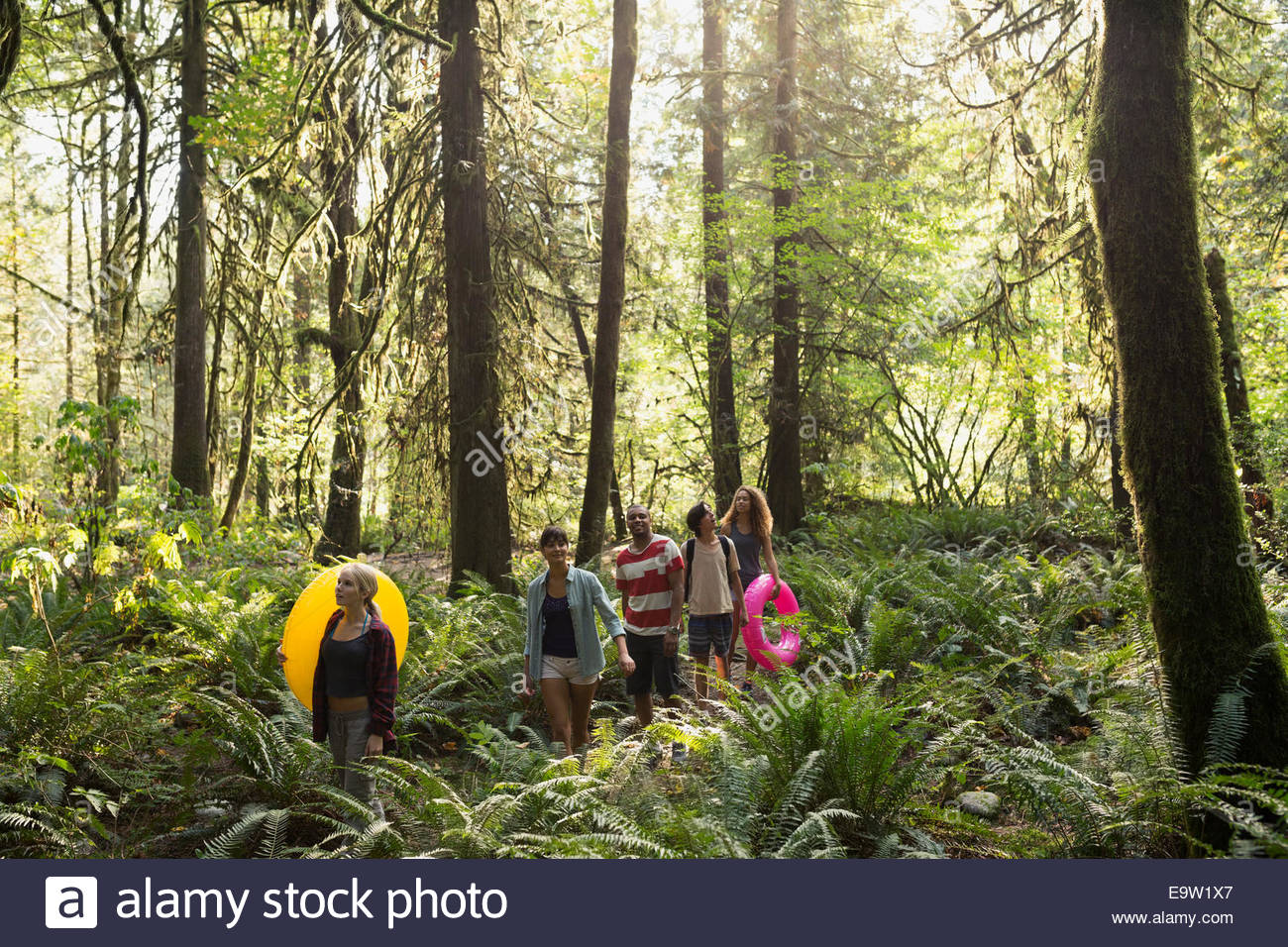 Friends with inflatable rings walking in woods - Stock Image