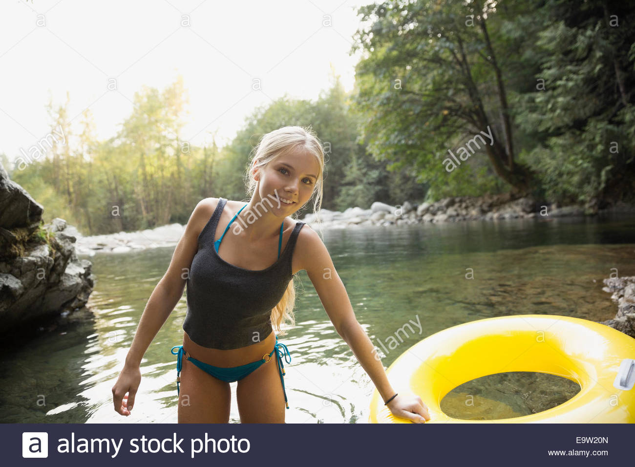 Young woman with inflatable ring at swimming hole - Stock Image