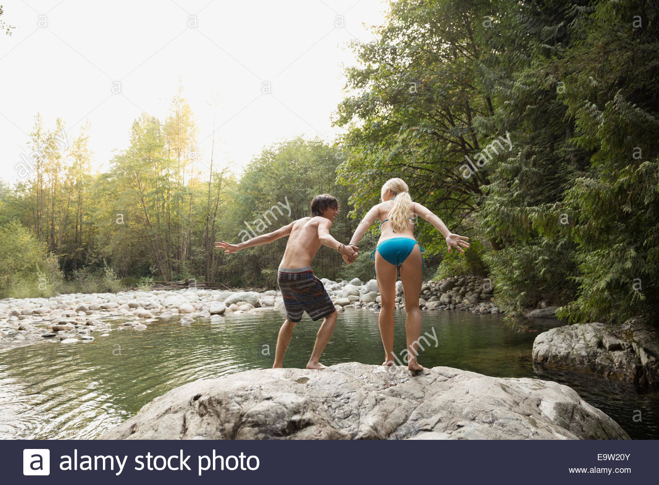Couple holding hands and jumping from rock Stock Photo