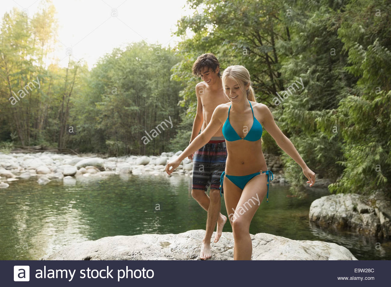Couple on rock at swimming hole - Stock Image