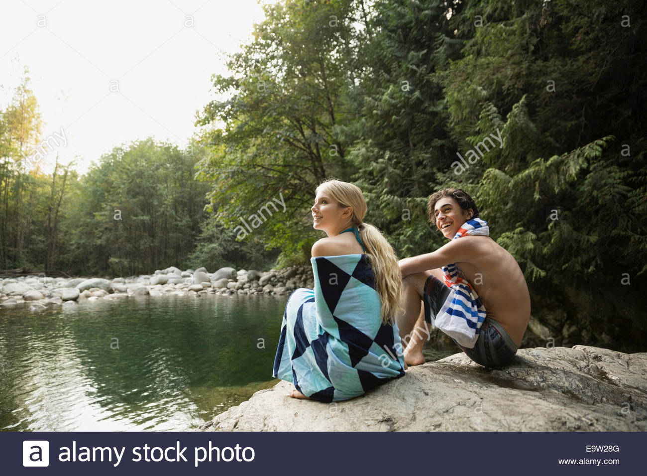 Couple wrapped in towel at swimming hole - Stock Image