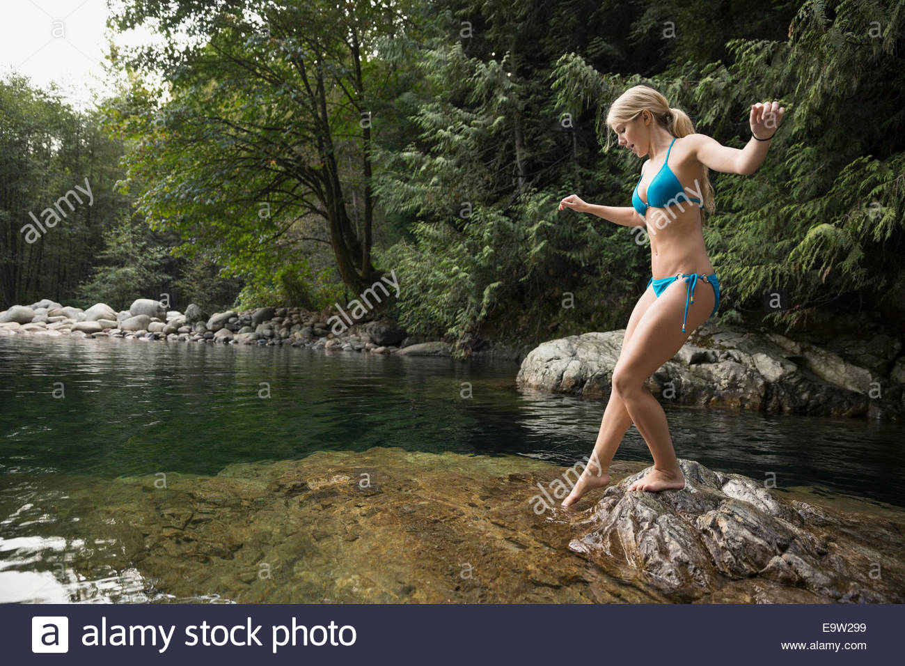 Young woman in bikini dipping toe in water - Stock Image