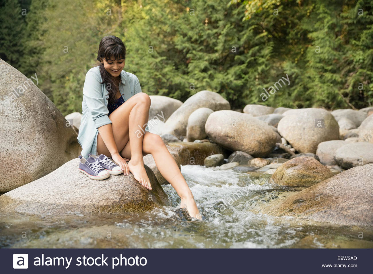 Woman dipping feet in creek in woods - Stock Image