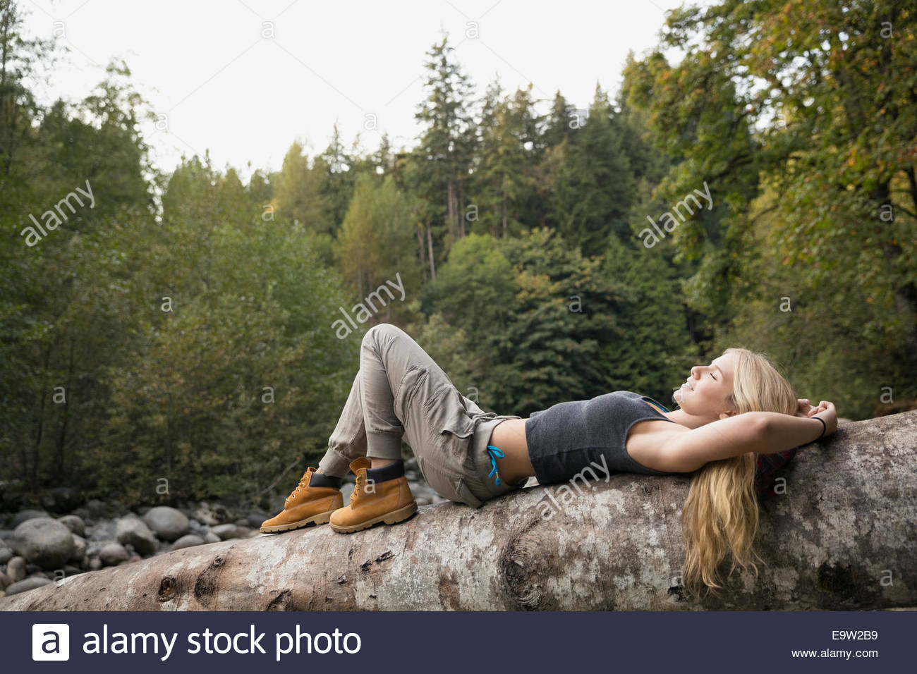 Young woman laying on fallen tree in woods - Stock Image