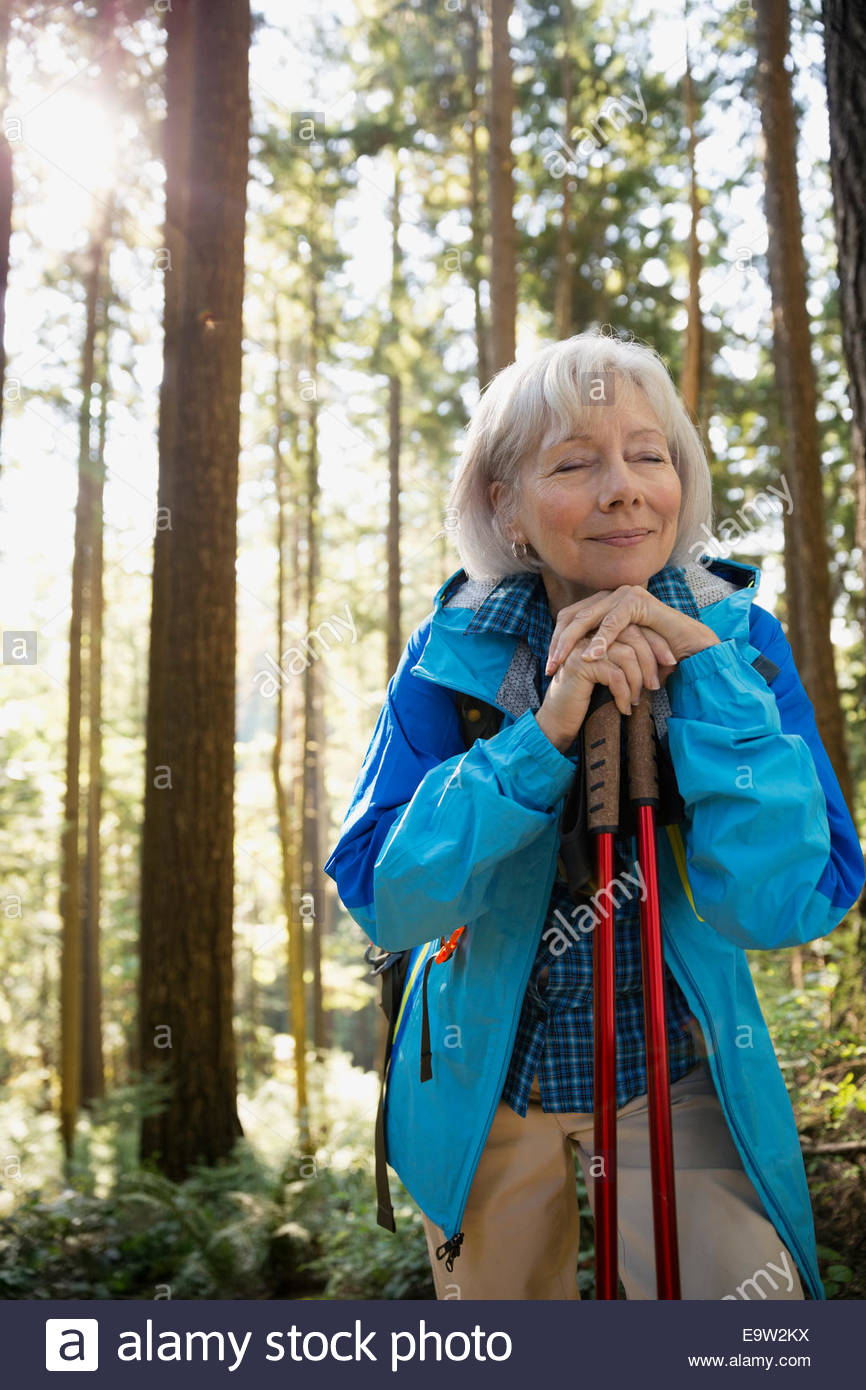 Serene senior woman hiking in sunny woods - Stock Image