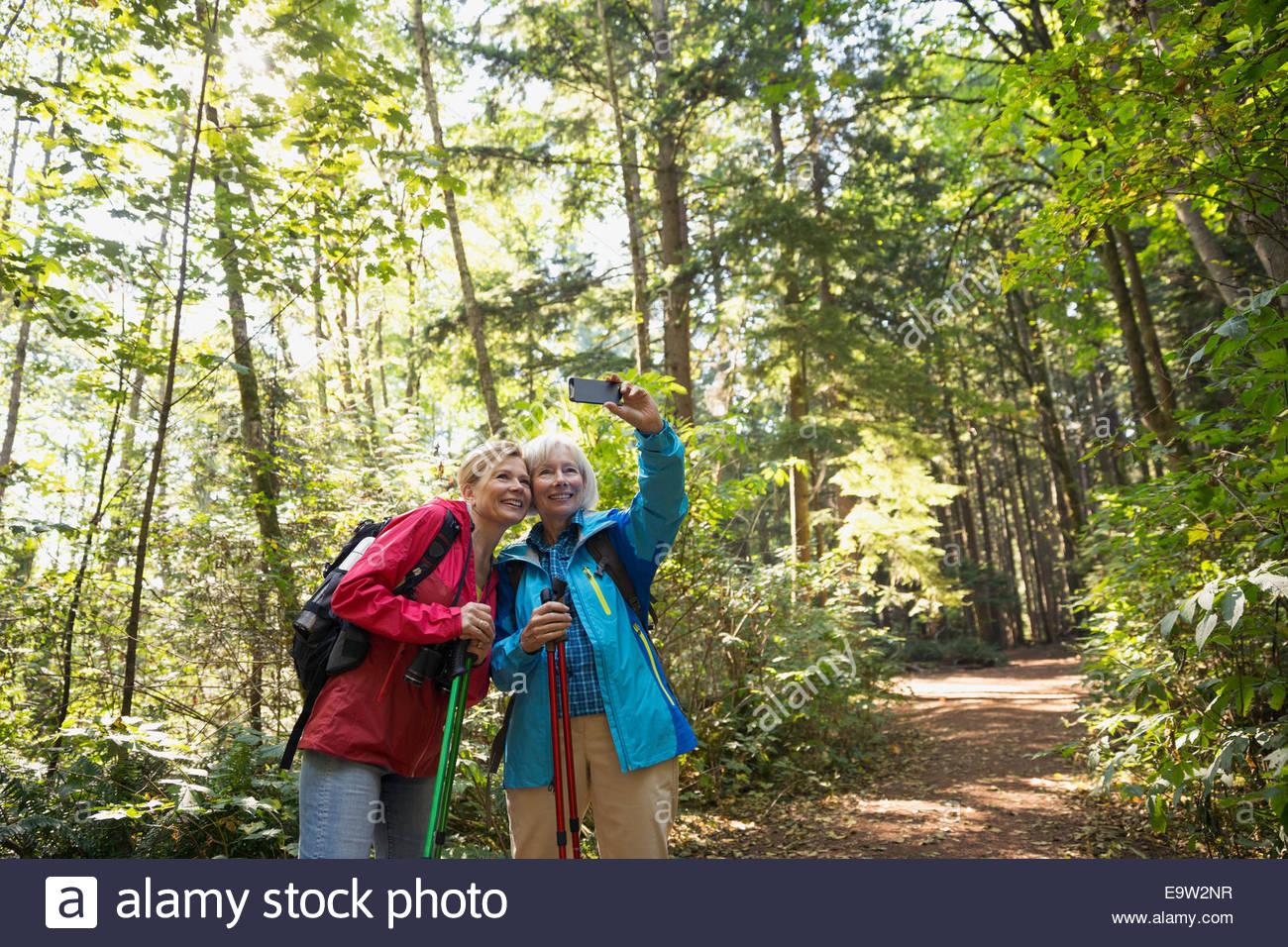 Women taking selfie on hiking trail in woods - Stock Image