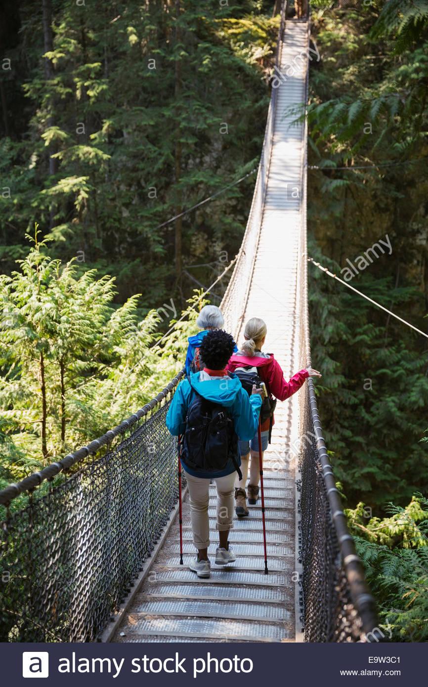 Women hiking across plank bridge in woods - Stock Image