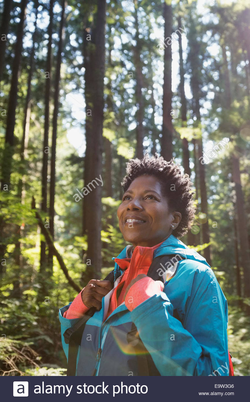 Smiling woman looking up in woods - Stock Image